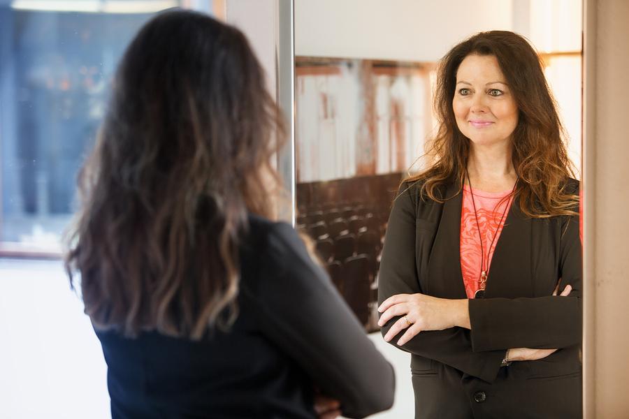 beautiful brunette woman looking at herself in mirror