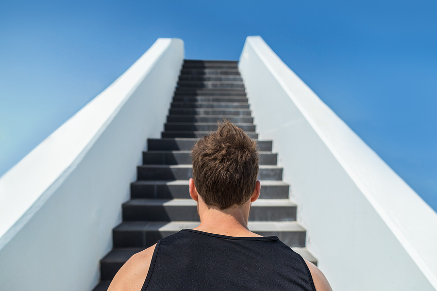 Fitness man looking ahead at stairs climbing challenge. Runner g
