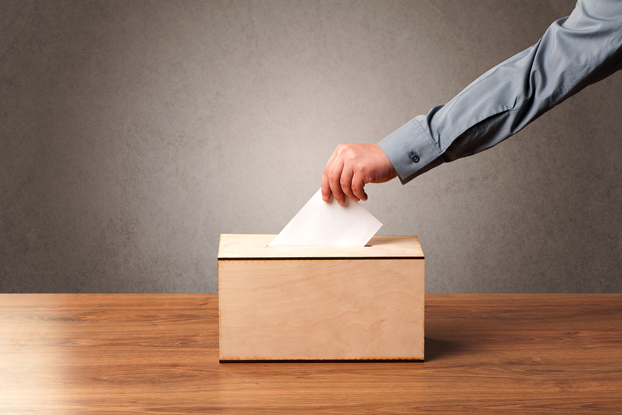 Ballot box with person casting vote on blank voting slip, grungy