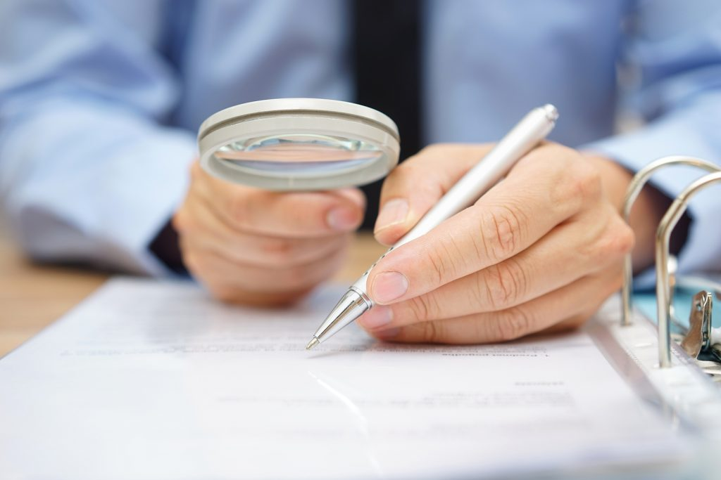 Businessman Is Analyzing  Through  Magnifying Glass Contract And