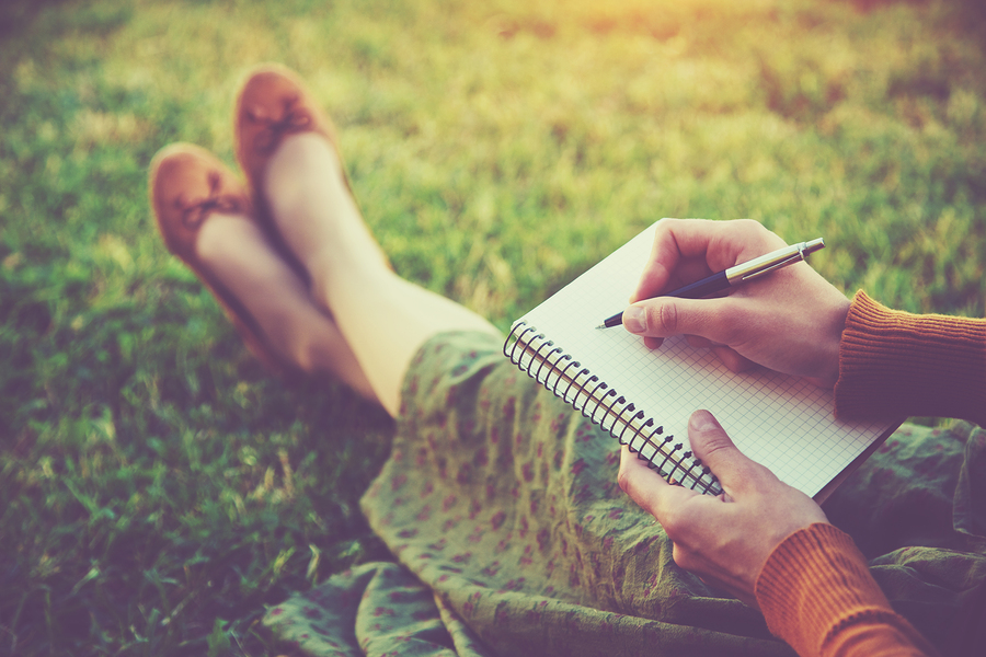 female hands with pen writing on notebook on grass outside