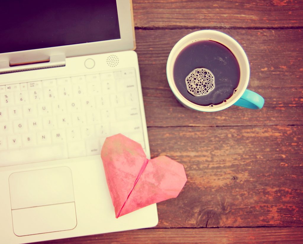 Computer with a paper heart and coffee - happy business concept