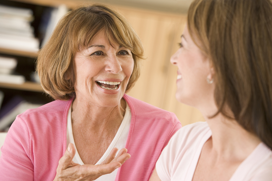 Two Women Sitting In Living Room Talking And Smiling