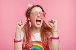 Overjoyed woman against a pink background