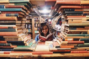 Girl in bookstore, framed by books