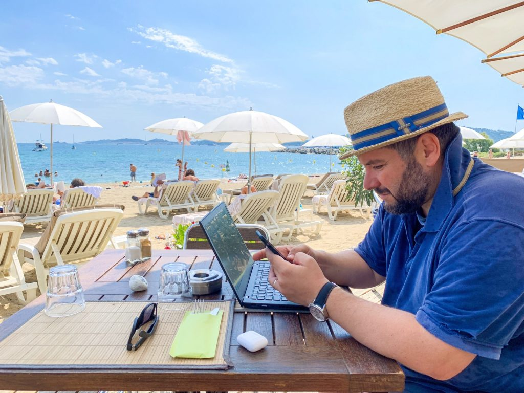 man-in-the-straw-hat-working-on-the-beach-sitting-at-the-table-with-his-laptop-and-mobile-phone_t20_zndJRJ