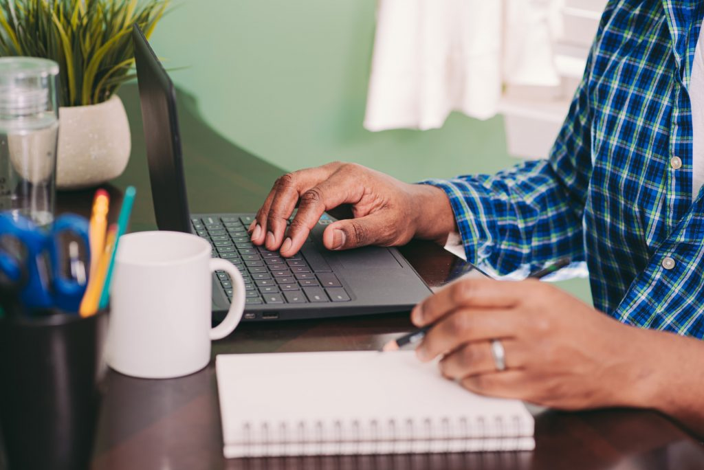 african-american-man-working-from-home-with-pencil-in-hand-and-coffee-cup-and-laptop-computer-in-the_t20_Bm4WNY