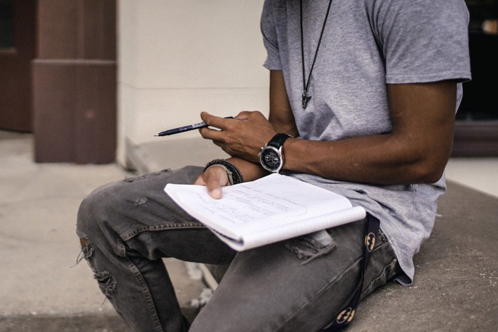 Writer making notes in a notebook