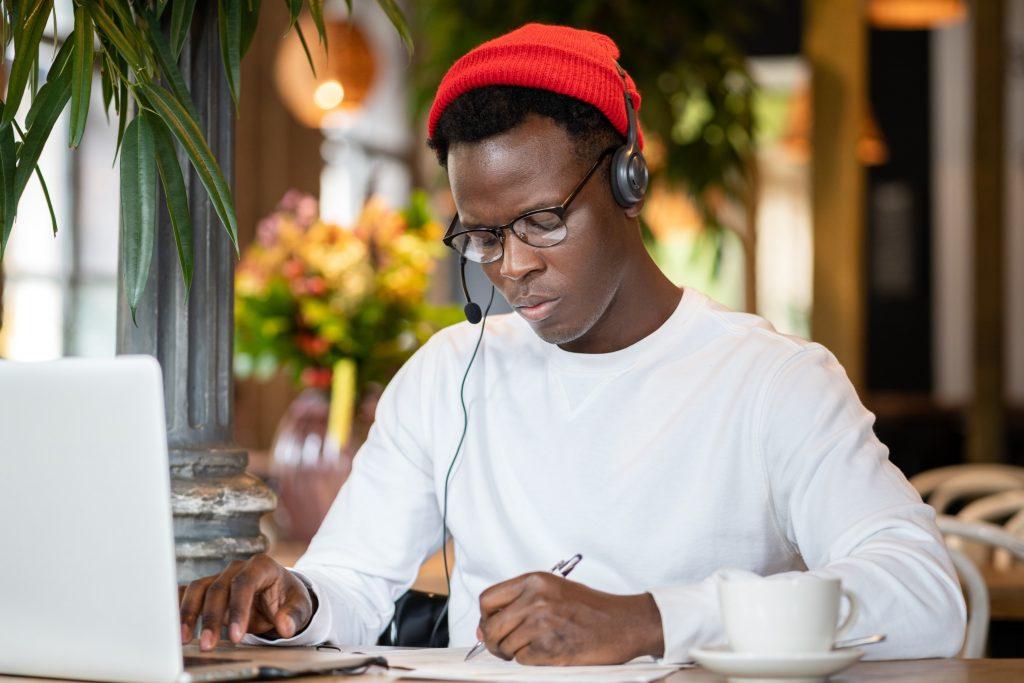 focused-millennial-black-man-in-headphones-wear-red-hat-watching-educational-webinar-on-laptop_t20_7yKgj6
