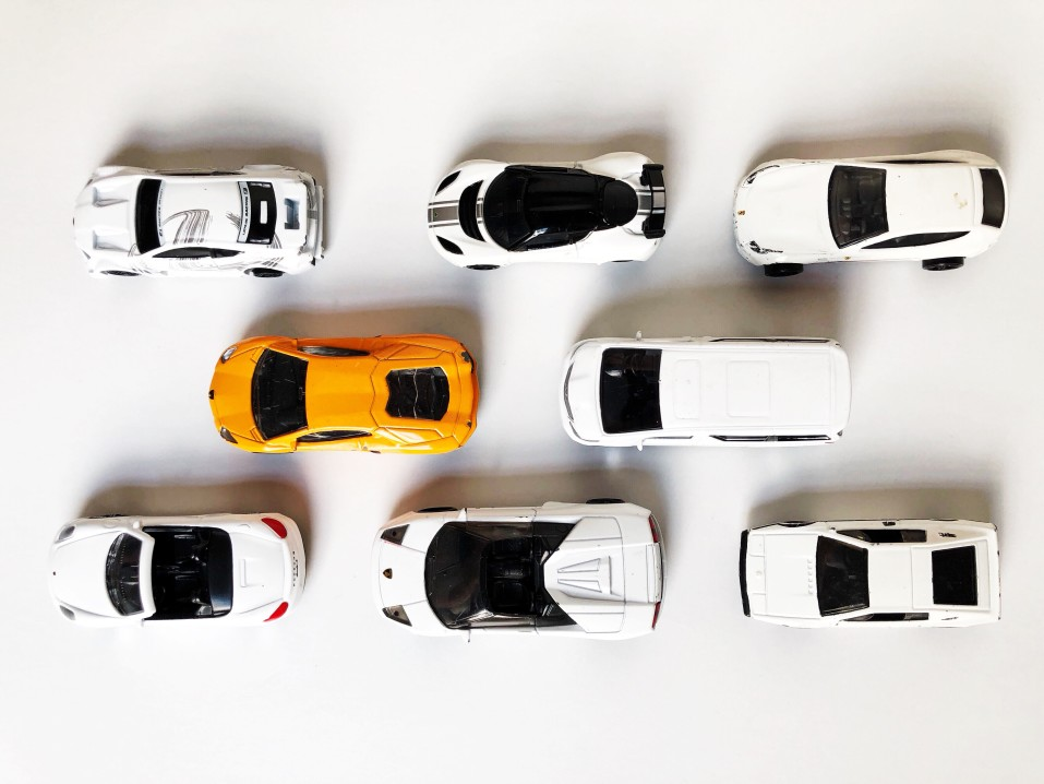 an-orange-toy-car-among-white-toy-cars-conceptual-theme-diversity-dare-to-be-different-be-unique-be_t20_moBVYr