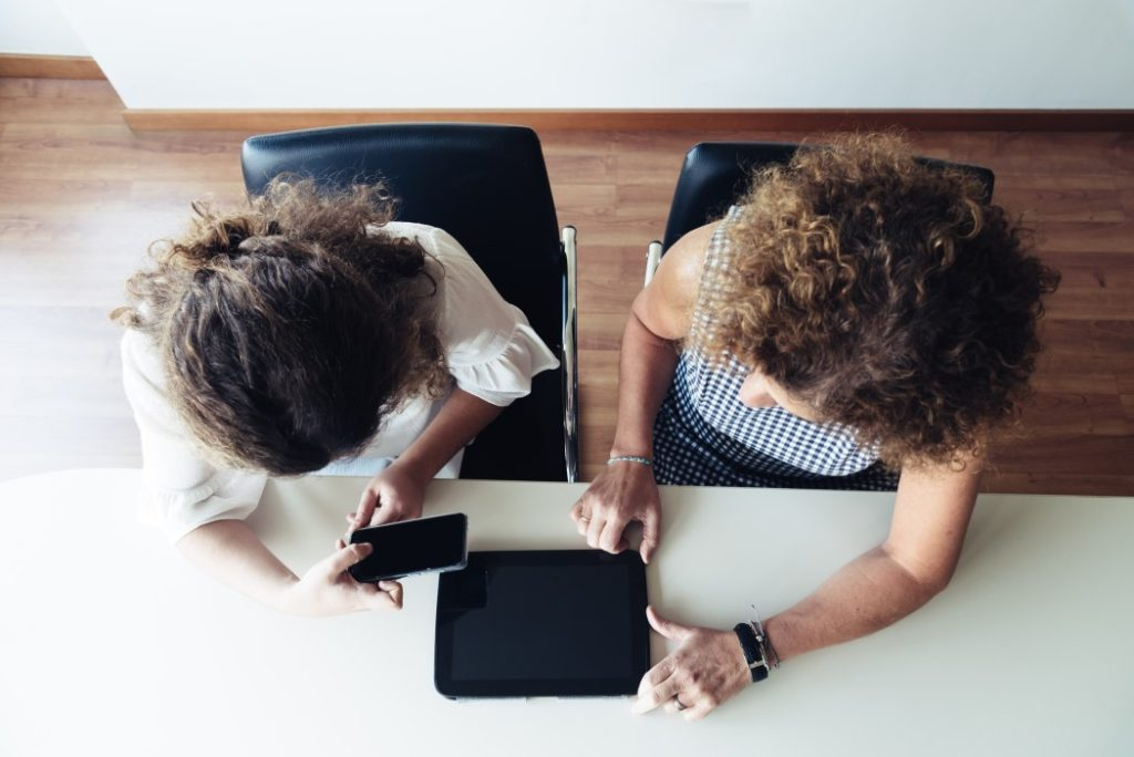 two-businesswomen-working-together-at-office-top-view-two-businesswoman-working-in-cooperation_t20_jRo9Aa