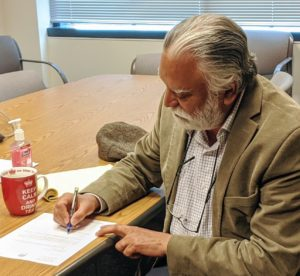 County Executive Satpal Sidhu signs Whatcom County's application to move to Phase 2 of Safe Start Washington.