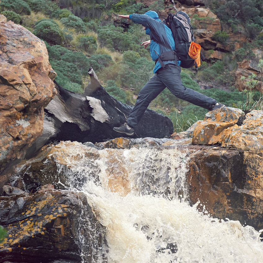 A hiker jumps across a stream above a waterfall