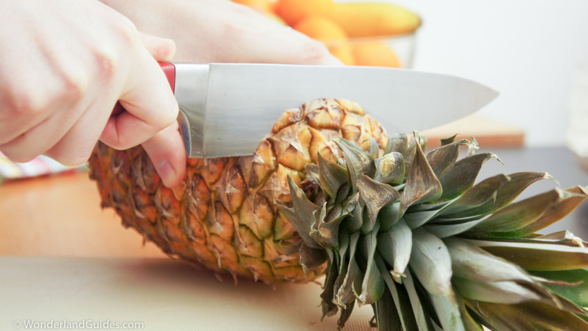chopping off the top of a pineapple