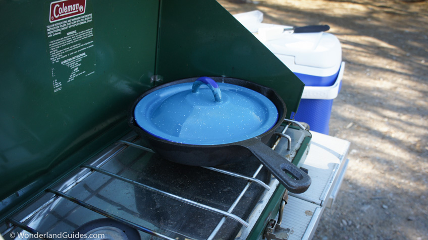 Skillet with a lid on a Coleman propane camping stove
