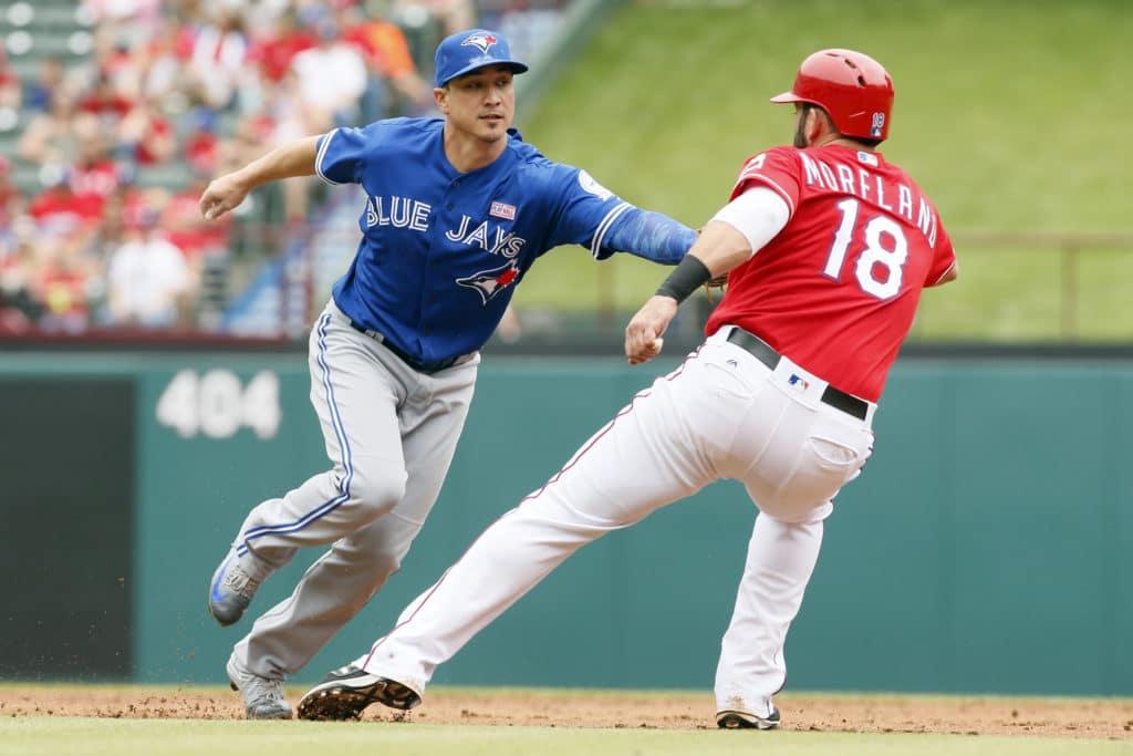 May 15, 2016; Arlington, TX, USA; Toronto Blue Jays second baseman Darwin Barney (18) tags out Texas Rangers first baseman Mitch Moreland (18) in the second inning at Globe Life Park in Arlington. Mandatory Credit: Tim Heitman-USA TODAY Sports