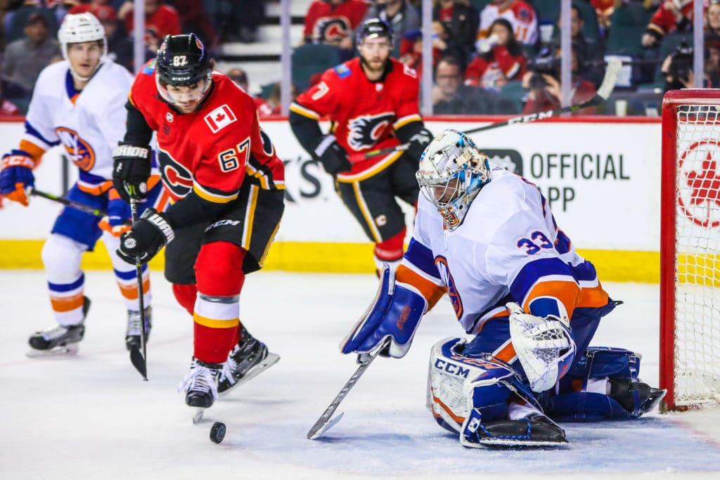 Mar 11, 2018; Calgary, Alberta, CAN; New York Islanders goaltender Christopher Gibson (33) makes a save against Calgary Flames right wing Michael Frolik (67) during the third period at Scotiabank Saddledome. Mandatory Credit: Sergei Belski-USA TODAY Sports