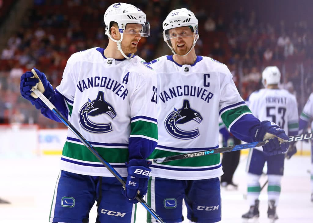 Mar 11, 2018; Glendale, AZ, USA; Vancouver Canucks left wing Daniel Sedin (left) with identical twin brother center Henrik Sedin in the second period against the Arizona Coyotes at Gila River Arena. Mandatory Credit: Mark J. Rebilas-USA TODAY Sports