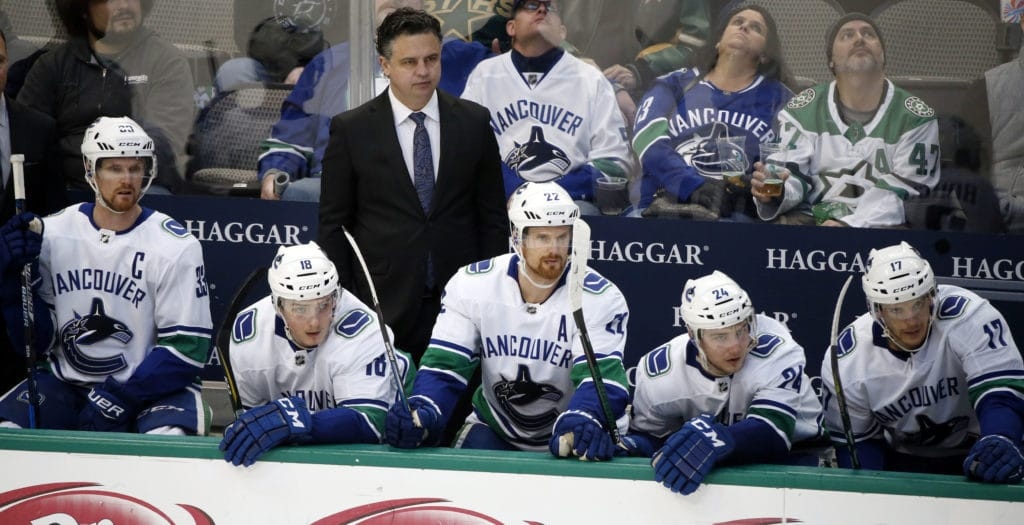 Vancouver Canucks head coach Travis Green watches his team play the Dallas Stars with center Henrik Sedin (33), right wing Jake Virtanen (18), left wing Daniel Sedin (22), center Reid Boucher (24) and center Nic Dowd (17) during the second period of an NHL hockey game in Dallas, Sunday, Feb. 11, 2018. (AP Photo/Michael Ainsworth)