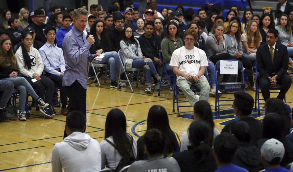 """Golden State Warriors coach Steve Kerr, left, speaks to Newark Memorial High School students on Monday, March 12, 2018, in Newark, Calif. Kerr joined Rep. Ro Khanna, D-Calif., seated at right, and Matt Deitsch, 20, wearing """"Stop Gun Violence"""" shirt, in a town hall style conversation on gun violence in America. Deitsch's younger brother and sister stayed locked in closets during last month's shooting at Marjory Stoneman Douglas High School in Parkland, Florida. (AP Photo/Ben Margot)"""