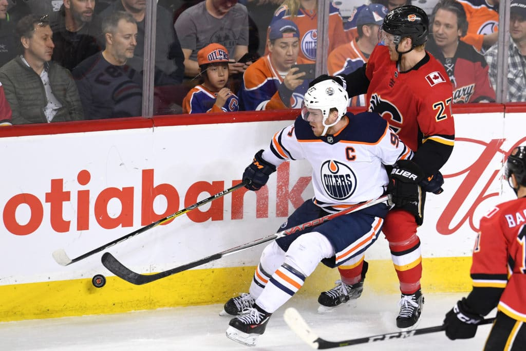 Mar 13, 2018; Calgary, Alberta, CAN; Edmonton Oilers center Connor McDavid (97) battles for the puck with defenseman Dougie Hamilton (27) during the third period at Scotiabank Saddledome. Mandatory Credit: Candice Ward-USA TODAY Sports