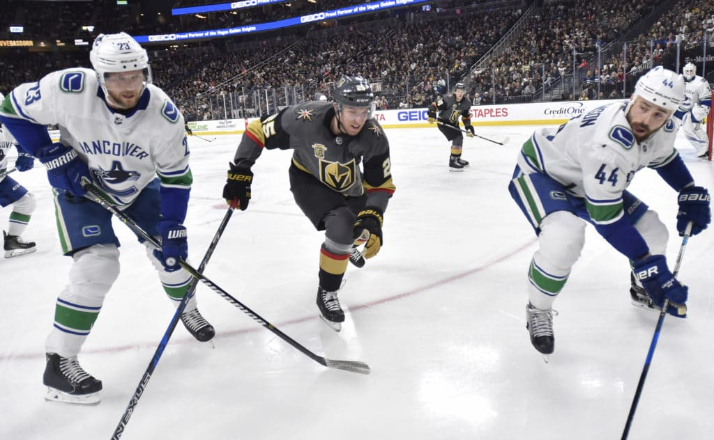 LAS VEGAS, NV - FEBRUARY 23:  Stefan Matteau #25 of the Vegas Golden Knights skates to the puck against Alexander Edler #23 and Erik Gudbranson #44 of the Vancouver Canucks during the game at T-Mobile Arena on February 23, 2018 in Las Vegas, Nevada.  (Photo by David Becker/NHLI via Getty Images)
