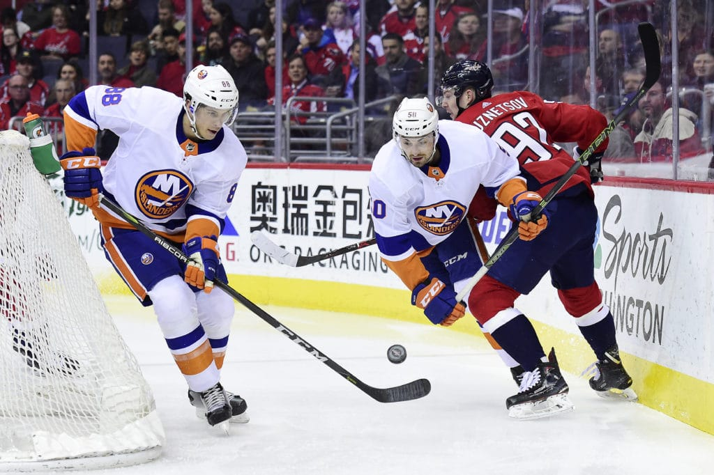 WASHINGTON, DC - MARCH 16: Brandon Davidson #88 and Adam Pelech #50 of the New York Islanders battle for the puck against Evgeny Kuznetsov #92 of the Washington Capitals in the first period at Capital One Arena on March 16, 2018 in Washington, DC. (Photo by Patrick McDermott/NHLI via Getty Images)