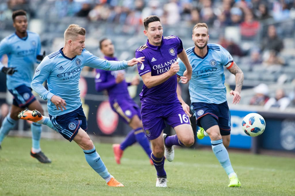 NEW YORK, NEW YORK - March 11: Sacha Kljestan #16 of Orlando City challenged by Alexander Ring #8 of New York City and Maxime Chanot #4 of New York City during the New York City FC Vs Orlando City SC regular season MLS game at Yankee Stadium on March 17, 2018 in New York City. (Photo by Tim Clayton/Corbis via Getty Images)