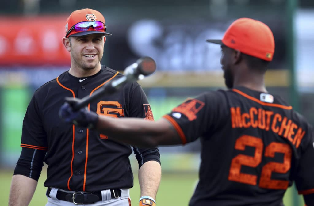 San Francisco Giants' Evan Longoria, left, speaks with Andrew McCutchen (22) during a spring training baseball practice on Monday, Feb. 19, 2018 in Scottsdale, Ariz. (AP Photo/Ben Margot)