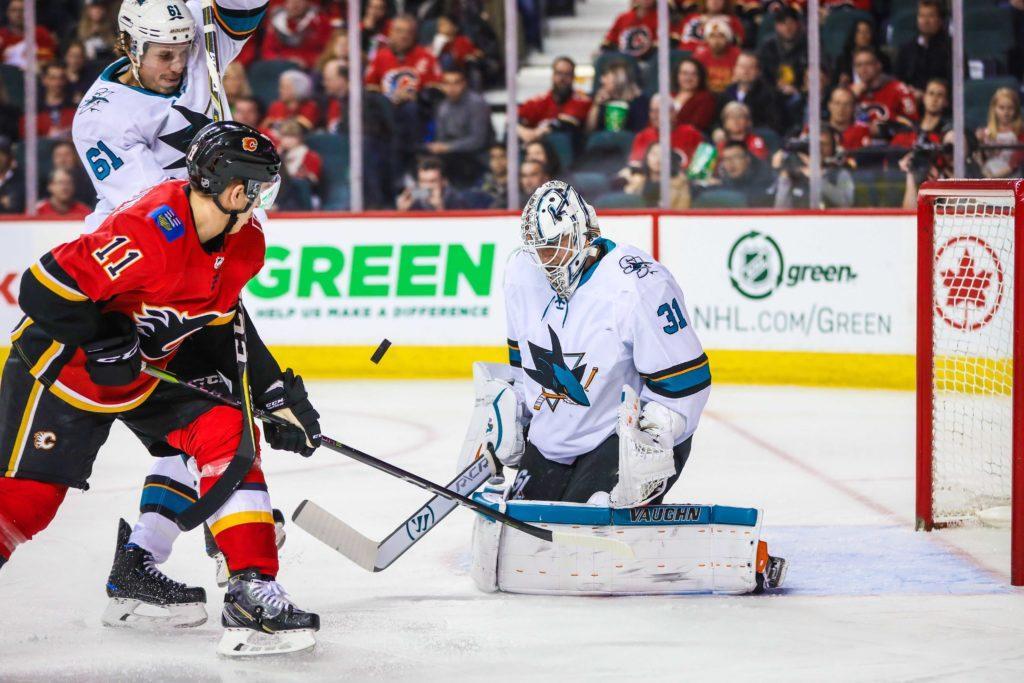Mar 16, 2018; Calgary, Alberta, CAN; San Jose Sharks goaltender Martin Jones (31) makes a save as Calgary Flames center Mikael Backlund (11) tries to score during the third period at Scotiabank Saddledome. San Jose Sharks won 7-4. Mandatory Credit: Sergei Belski-USA TODAY Sports