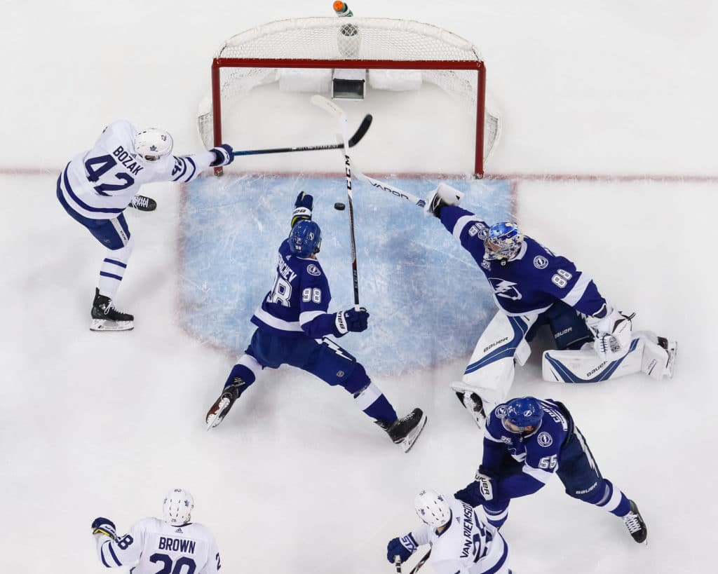 TAMPA, FL - MARCH 20: Goalie Andrei Vasilevskiy #88 and Mikhail Sergachev #98 of the Tampa Bay Lightning  dive for the puck against Tyler Bozak #42 of the Toronto Maple Leafs during the first period at Amalie Arena on March 20, 2018 in Tampa, Florida. (Photo by Scott Audette/NHLI via Getty Images)