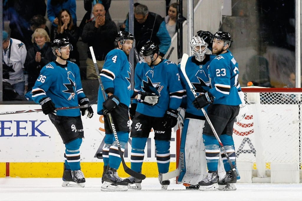 SAN JOSE, CA - MARCH 20: Brenden Dillon #4, Dylan DeMelo #74, Martin Jones #31, and Barclay Goodrow #23 of the San Jose Sharks celebrate the win against the New Jersey Devils at SAP Center on March 20, 2018 in San Jose, California. The Sharks defeated the Devils 6-2. (Photo by Don Smith/NHLI via Getty Images)