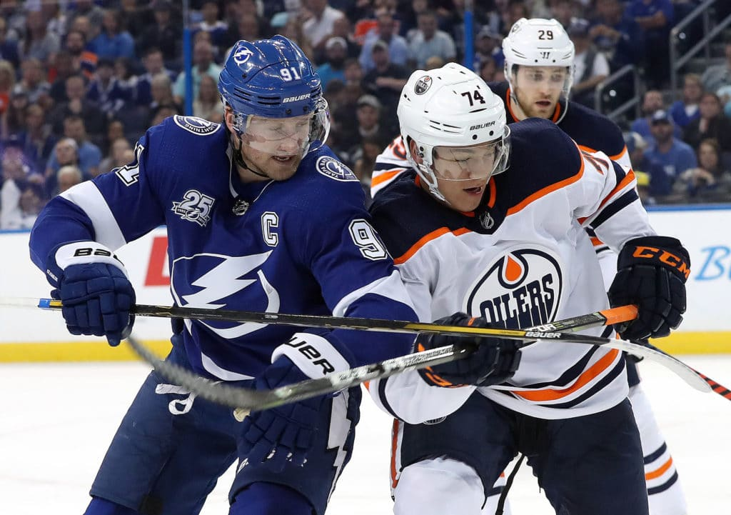 Mar 18, 2018; Tampa, FL, USA; Tampa Bay Lightning center Steven Stamkos (91) and Edmonton Oilers defenseman Ethan Bear (74) fight to control the puck during the second period at Amalie Arena. Mandatory Credit: Kim Klement-USA TODAY Sports