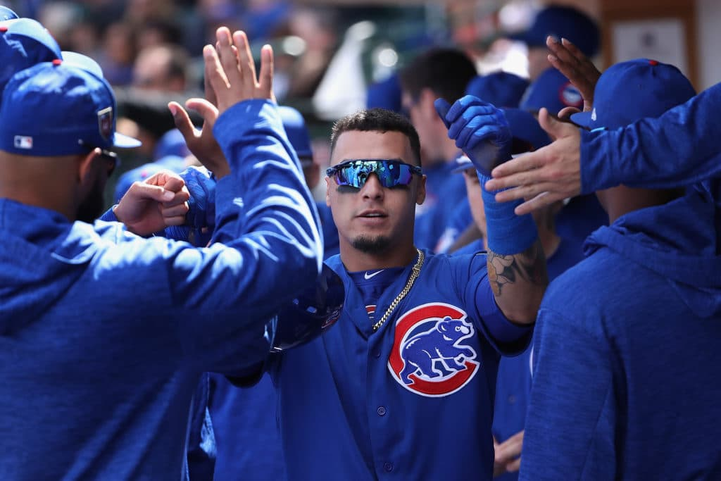 MESA, AZ - FEBRUARY 28:  Javier Baez #9 of the Chicago Cubs high fives teammates in the dugout after scoring a run against the Oakland Athletics during the first inning of the spring training game at Sloan Park on February 28, 2018 in Mesa, Arizona.  (Photo by Christian Petersen/Getty Images)