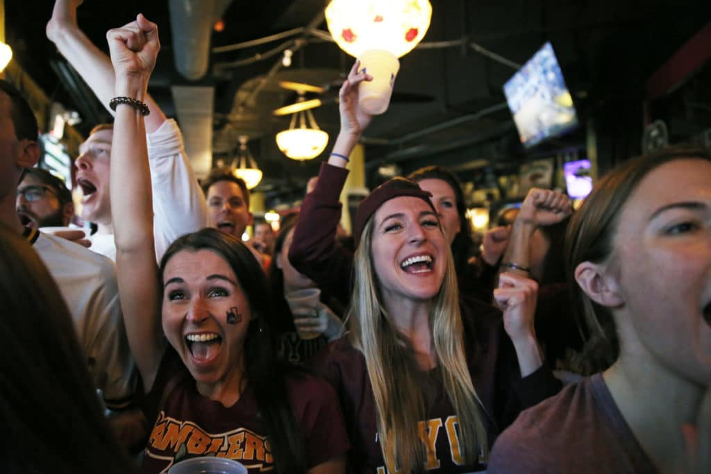 Kelly Scott, left, and Alyvia Clark, right, join other alums during a watch party in Chicago as Loyola knocks out Kansas State, 78-62, in an NCAA Tournament regional final at Philips Arena in Atlanta on Saturday, March 24, 2018. (Nuccio DiNuzzo/Chicago Tribune/TNS via Getty Images)