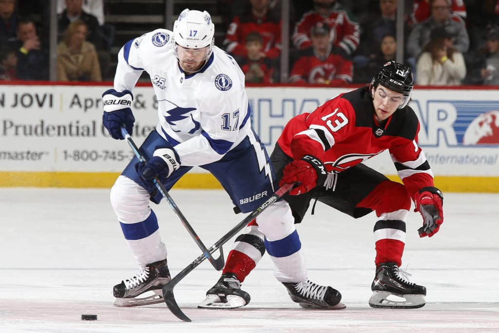 NEWARK, NJ - MARCH 24: Alex Killorn #17 of the Tampa Bay Lightning and Nico Hischier #13 of the New Jersey Devils battle for the puck during the second period at the Prudential Center on March 24, 2018 in Newark, New Jersey. (Photo by Adam Hunger/Getty Images)