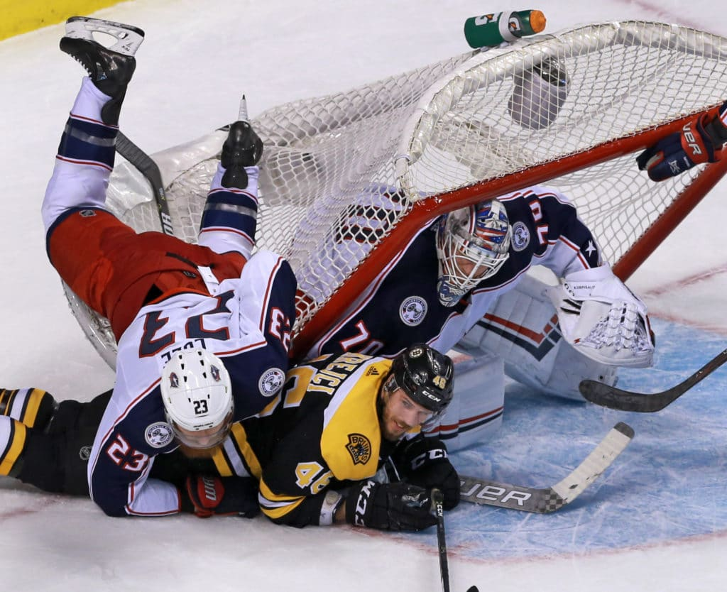 BOSTON - MARCH 19: The net ends up on top of the Bruins' David Krejci as he and the Blue Jackets' Ian Cole, left, battle in the second period. The Boston Bruins host the Columbus Blue Jackets in a regular season NHL hockey game at TD Garden in Boston on March 19, 2018. (Photo by Jim Davis/The Boston Globe via Getty Images)