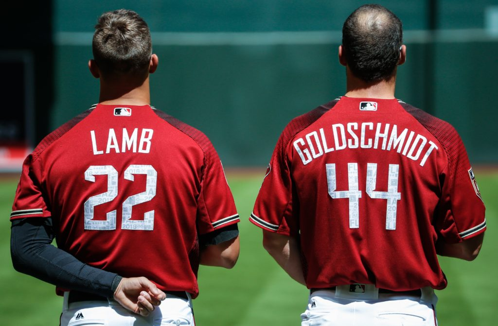 PHOENIX, AZ - MARCH 27:  Arizona Diamondbacks third baseman Jake Lamb (22) and Arizona Diamondbacks first baseman Paul Goldschmidt (44) line up for the national anthem before the spring training MLB baseball game between the Cleveland Indians and the Arizona Diamondbacks on March 27, 2018 at Chase Field in Phoenix, Arizona. (Photo by Kevin Abele/Icon Sportswire via Getty Images)