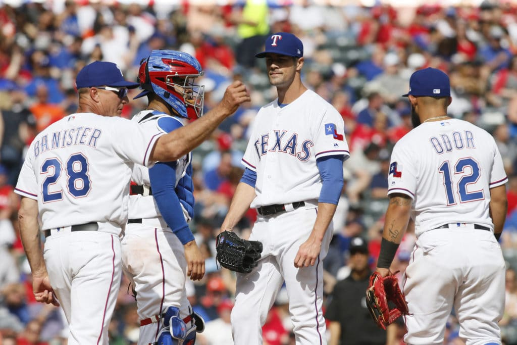Mar 29, 2018; Arlington, TX, USA; Texas Rangers manager Jeff Banister (28) motions to the bullpen with starting pitcher Cole Hamels (35) and catcher Robinson Chirinos (61) and second baseman Rougned Odor (12) at the mound in the sixth inning against the Houston Astros at Globe Life Park in Arlington. Mandatory Credit: Tim Heitman-USA TODAY Sports