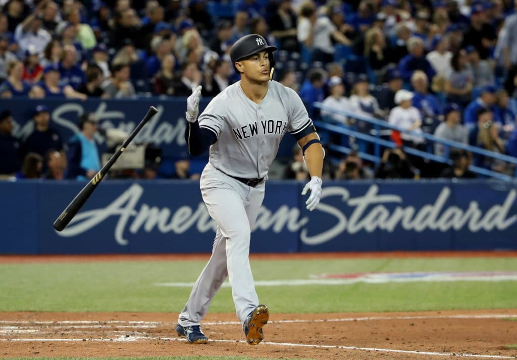 TORONTO, ON - MARCH 29: Giancarlo Stanton #27 of the New York Yankees reacts as he hits a solo home run in the ninth inning on Opening Day during MLB game action against the Toronto Blue Jays at Rogers Centre on March 29, 2018 in Toronto, Canada. (Photo by Tom Szczerbowski/Getty Images)