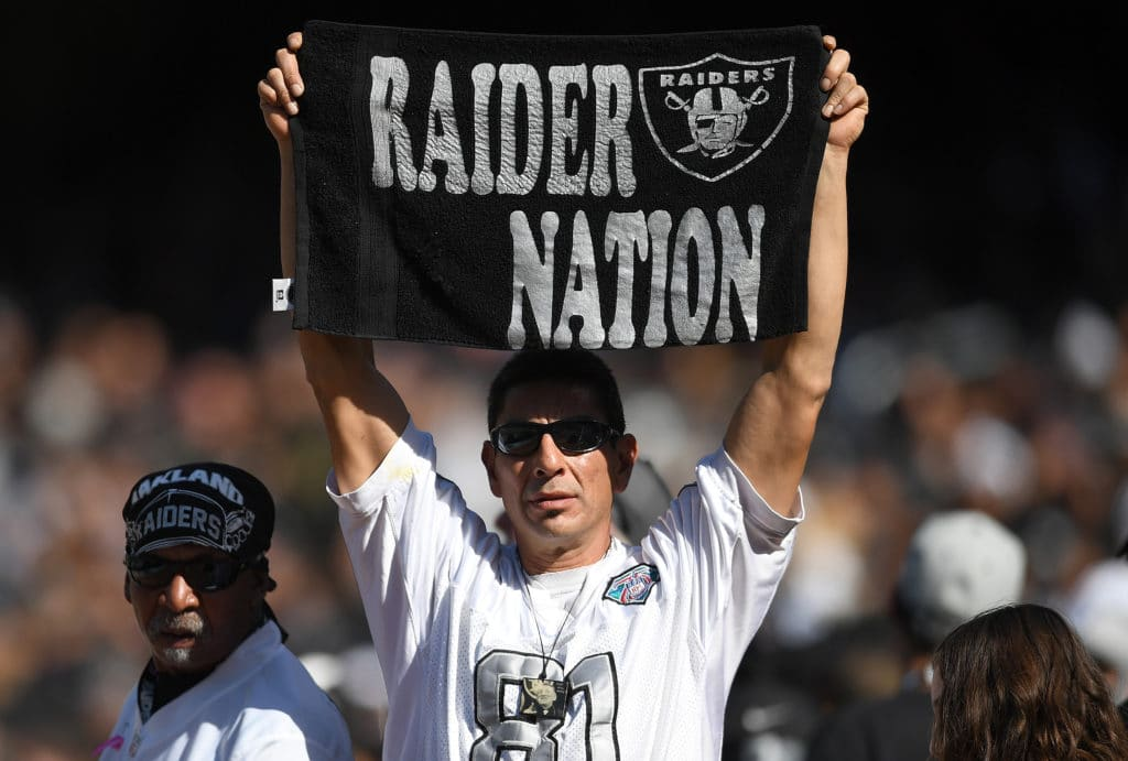 """OAKLAND, CA - OCTOBER 08:  A fan in the stands holds up a towl reading """"Raider Nation"""" during an NFL football game between the Baltimore Ravens and Oakland Raiders at Oakland-Alameda County Coliseum on October 8, 2017 in Oakland, California.  (Photo by Thearon W. Henderson/Getty Images)"""