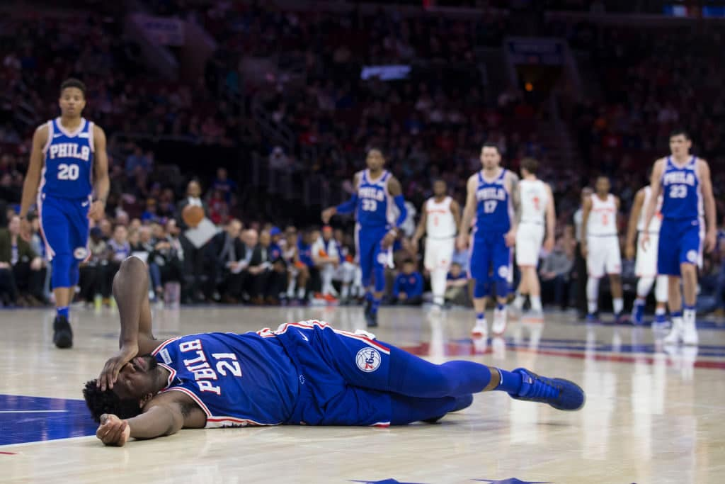 PHILADELPHIA, PA - MARCH 28: Joel Embiid #21 of the Philadelphia 76ers lies on the court after a collision with Markelle Fultz #20 of the Philadelphia 76ers in the second quarter against the New York Knicks at the Wells Fargo Center on March 28, 2018 in Philadelphia, Pennsylvania. NOTE TO USER: User expressly acknowledges and agrees that, by downloading and or using this photograph, User is consenting to the terms and conditions of the Getty Images License Agreement. (Photo by Mitchell Leff/Getty Images)