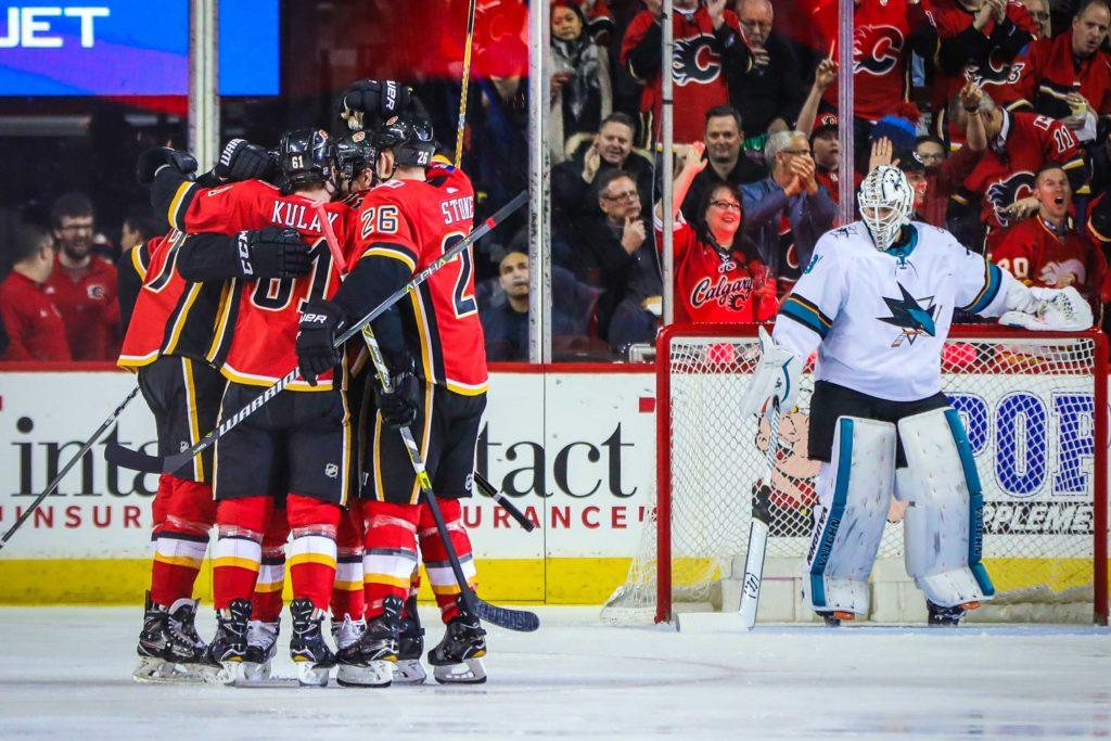 Mar 16, 2018; Calgary, Alberta, CAN; Calgary Flames center Mark Jankowski (77) celebrates his goal with teammates in front of San Jose Sharks goaltender Martin Jones (31) during the second period at Scotiabank Saddledome. Mandatory Credit: Sergei Belski-USA TODAY Sports