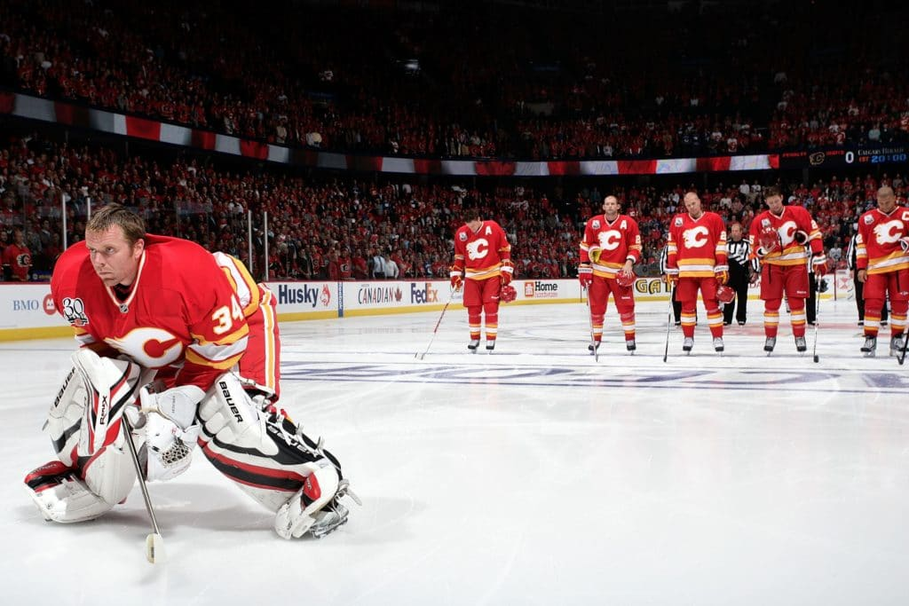 CALGARY, AB - OCTOBER 1:  Miikka Kiprusoff #34 stands with Dion Phaneuf #3, Robyn Regehr #28, Olli Jokinen #21, David Moss #25 and Jarome Iginla #12 of the Calgary Flames during the national anthems before the game against the Vancouver Canucks on October 1, 2009 at Pengrowth Saddledome in Calgary, Alberta, Canada. The Flames won 5-3. (Photo by Gerry Thomas/NHLI via Getty Images)