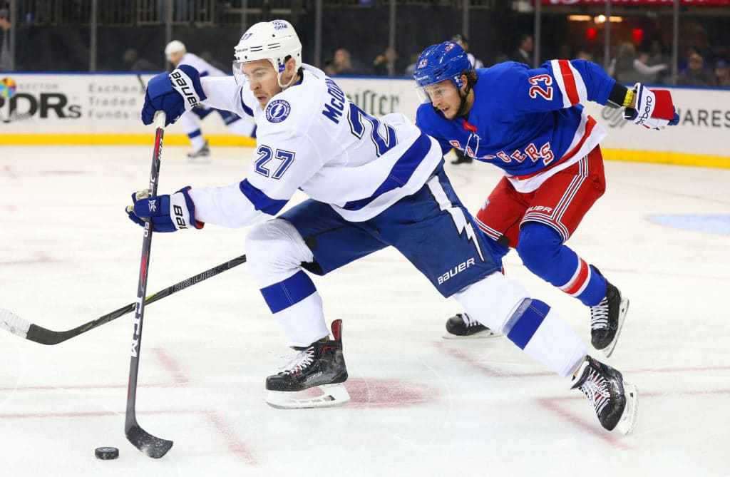 Mar 30, 2018; New York, NY, USA; Tampa Bay Lightning defenseman Ryan McDonagh (27) plays the puck while being pursued by New York Rangers center Ryan Spooner (23) during the second period at Madison Square Garden. Mandatory Credit: Andy Marlin-USA TODAY Sports