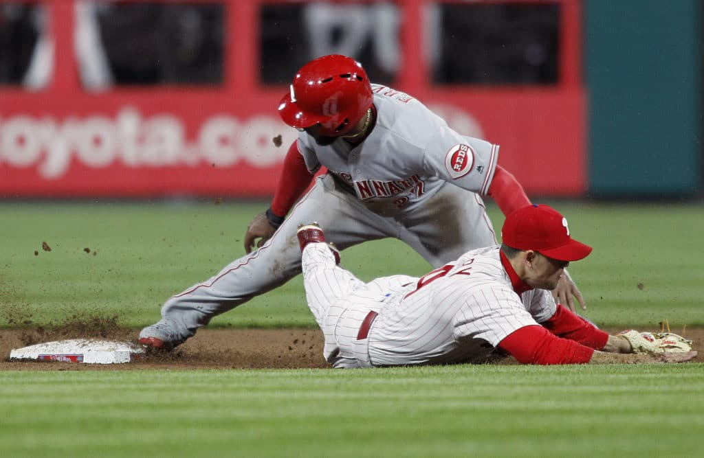 Cincinnati Reds' Phillip Ervin, top, is safe at second base after dodging the tag of Philadelphia Phillies' Scott Kingery, bottom, during the sixth inning of a baseball game Monday, April 9, 2018, in Philadelphia, Pa. (AP Photo/Tom Mihalek)