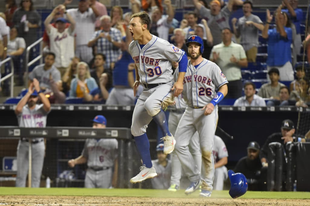 MIAMI, FL - APRIL 11: Michael Conforto #30 of the New York Mets jumps in the air after scoring the go ahead run in the eighth inning against the Miami Marlins at Marlins Park on April 11, 2018 in Miami, Florida. (Photo by Eric Espada/Getty Images)