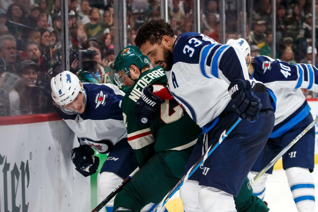 Apr 17, 2018; Saint Paul, MN, USA; Winnipeg Jets defensemen Dustin Byfuglien (33) skates after the puck in the second period against Minnesota Wild forward Nino Niederreiter (22) in game four of the first round of the 2018 Stanley Cup Playoffs at Xcel Energy Center. Mandatory Credit: Brad Rempel-USA TODAY Sports