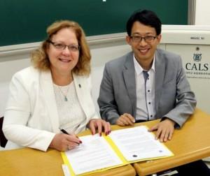 Rasco and Kang signing paperwork together
