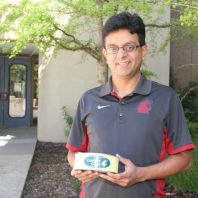 Interim director, Dr. Ganjyal, holding a can of Cougar Gold Cheese